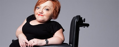 Stella Young sits in her motorised wheelchair and smiles for the camera