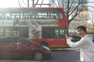 Laurie points to a 'Neighbours' advertisement on a red double decker bus in London