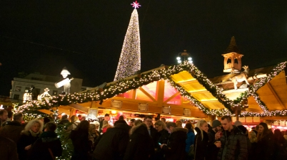 Christmas markets in Hamburg, people drinking wine in front of a stand with lit up Christmas tree in the background