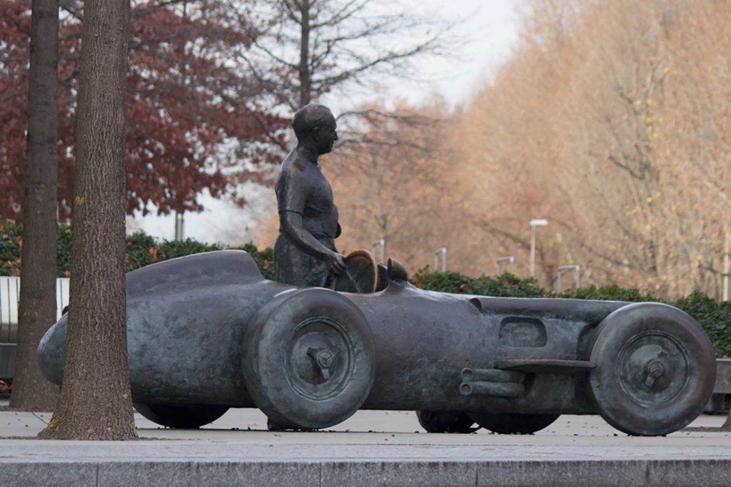 statue of a man and f1 car outside the mercedes-benz factory